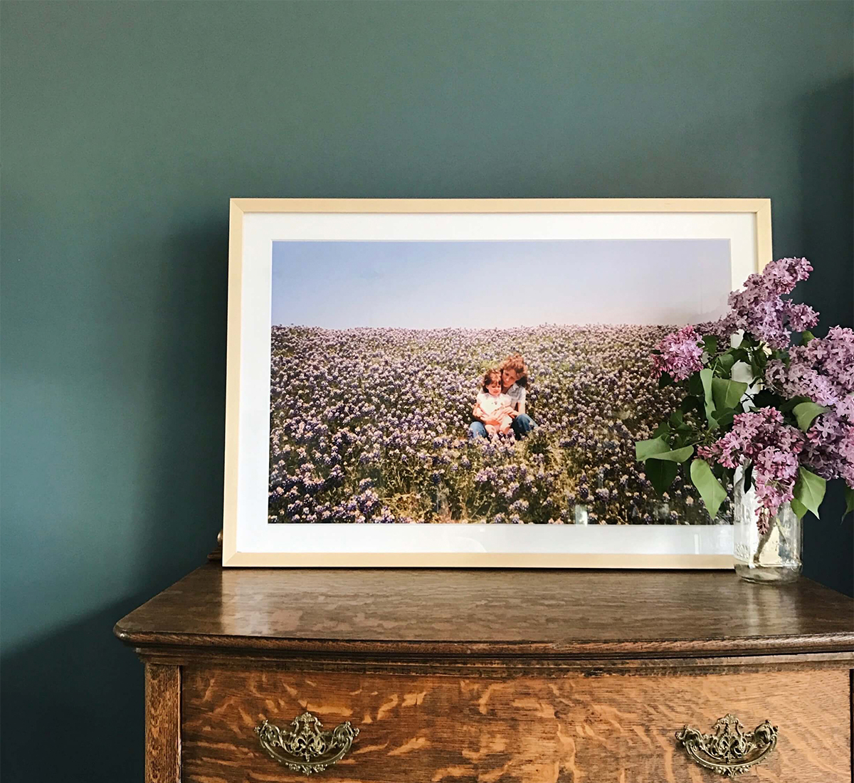 Gallery frame with vintage mother and daughter photo resting on dresser