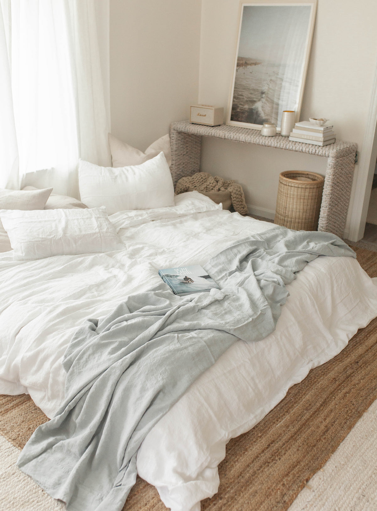 Bedroom with white bedspread, wicker furniture, and light neutral palette