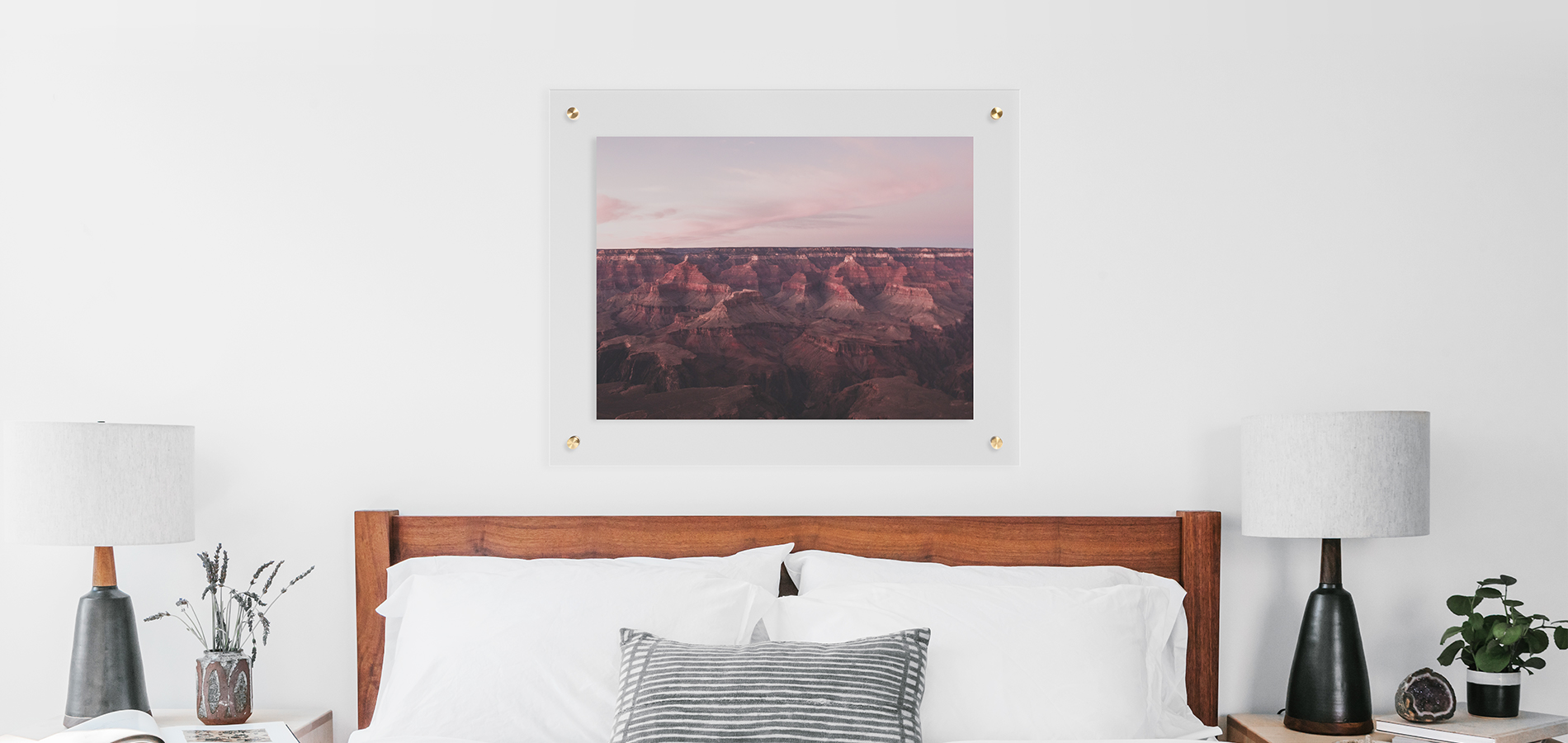Floating frame hung above bed with white linens in minimalist bedroom