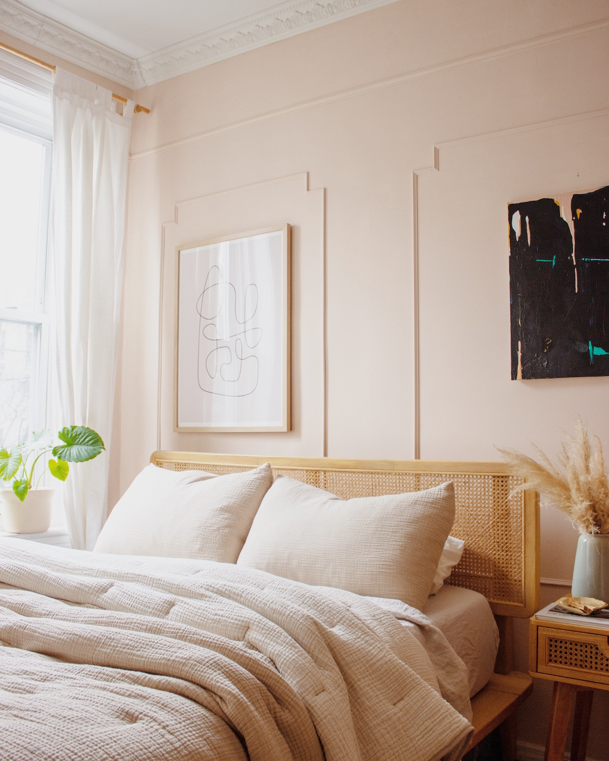 Bedroom decorated in all blush with small plant in corner