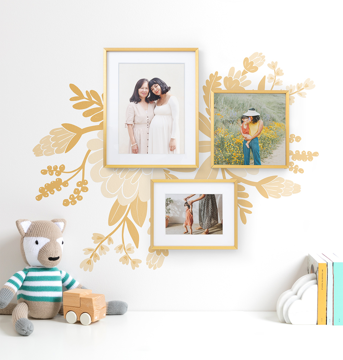Three small frames hung over top of a mural on nursery wall
