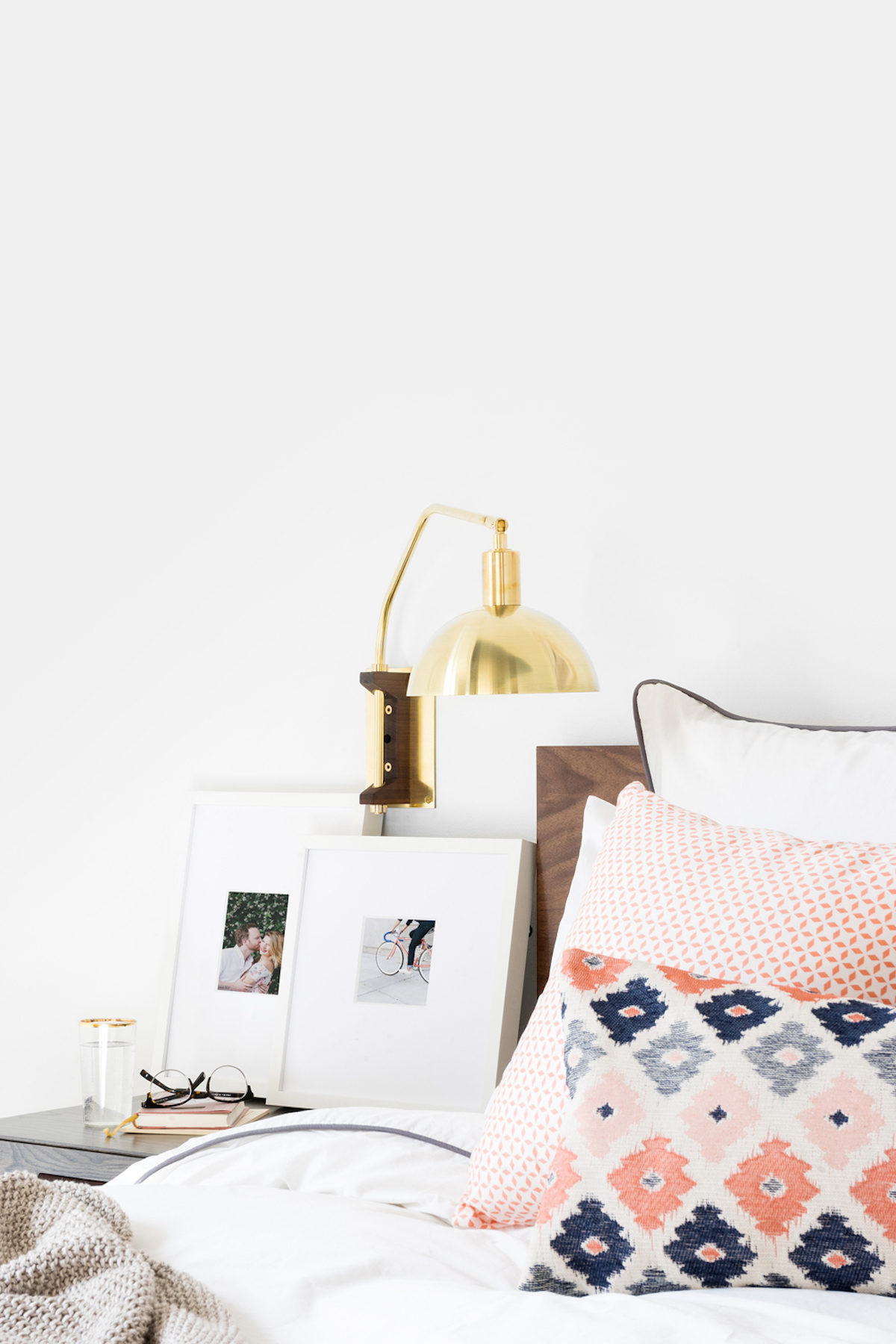 Two white frames on nightstand resting in layered fashion against the wall