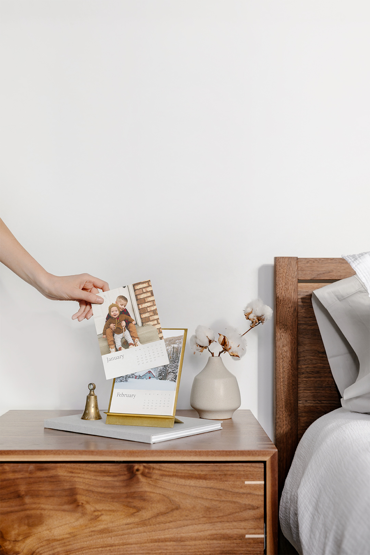 Woman's hand changing month on nightstand calendar