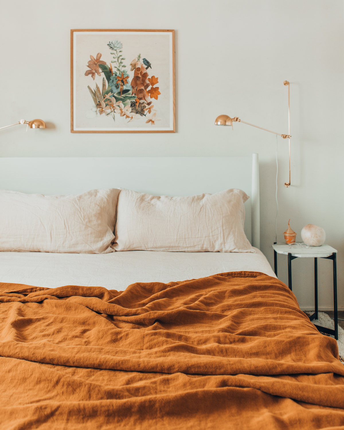 Burnt orange bedspread in an otherwise white room