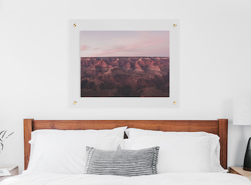 floating frame of desert landscape above bed with white bedding