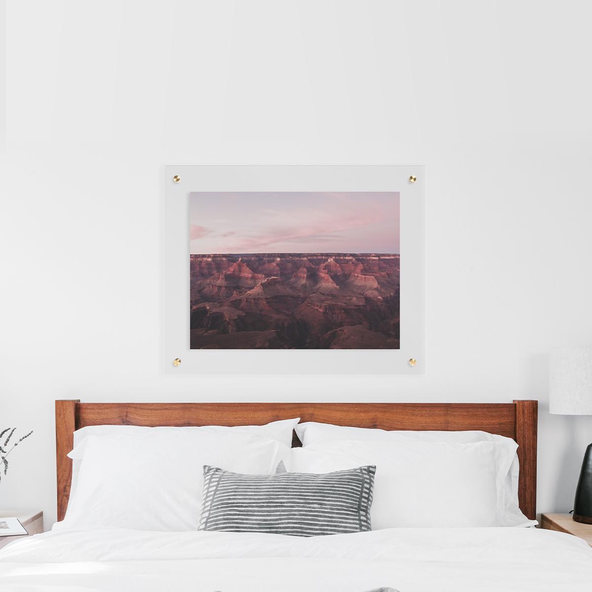 Floating frame with desert landscape hanging above white bed