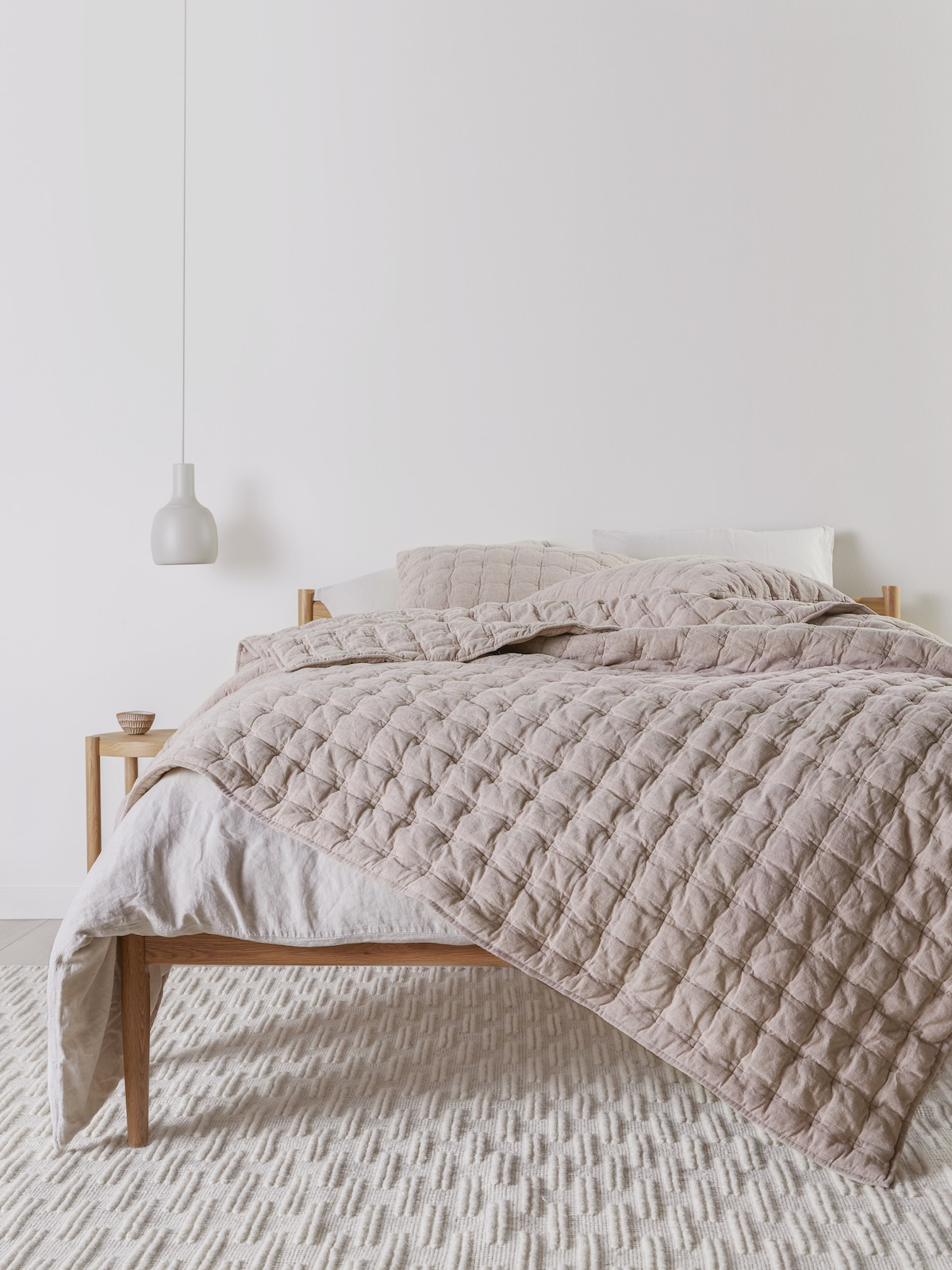 Quilted blush bedspread on unmade bed