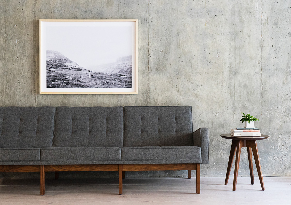 Large framed photo of couple in desert landscape hung above gray couch