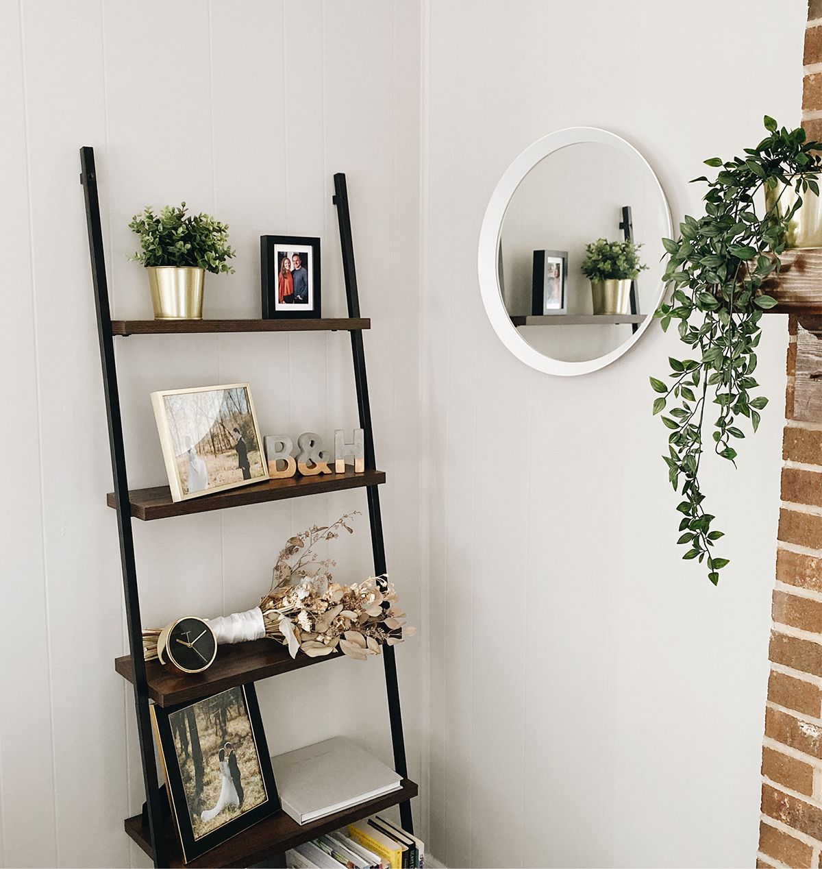 Photo by Brian Schindler of shelving display with photos frames and small plants