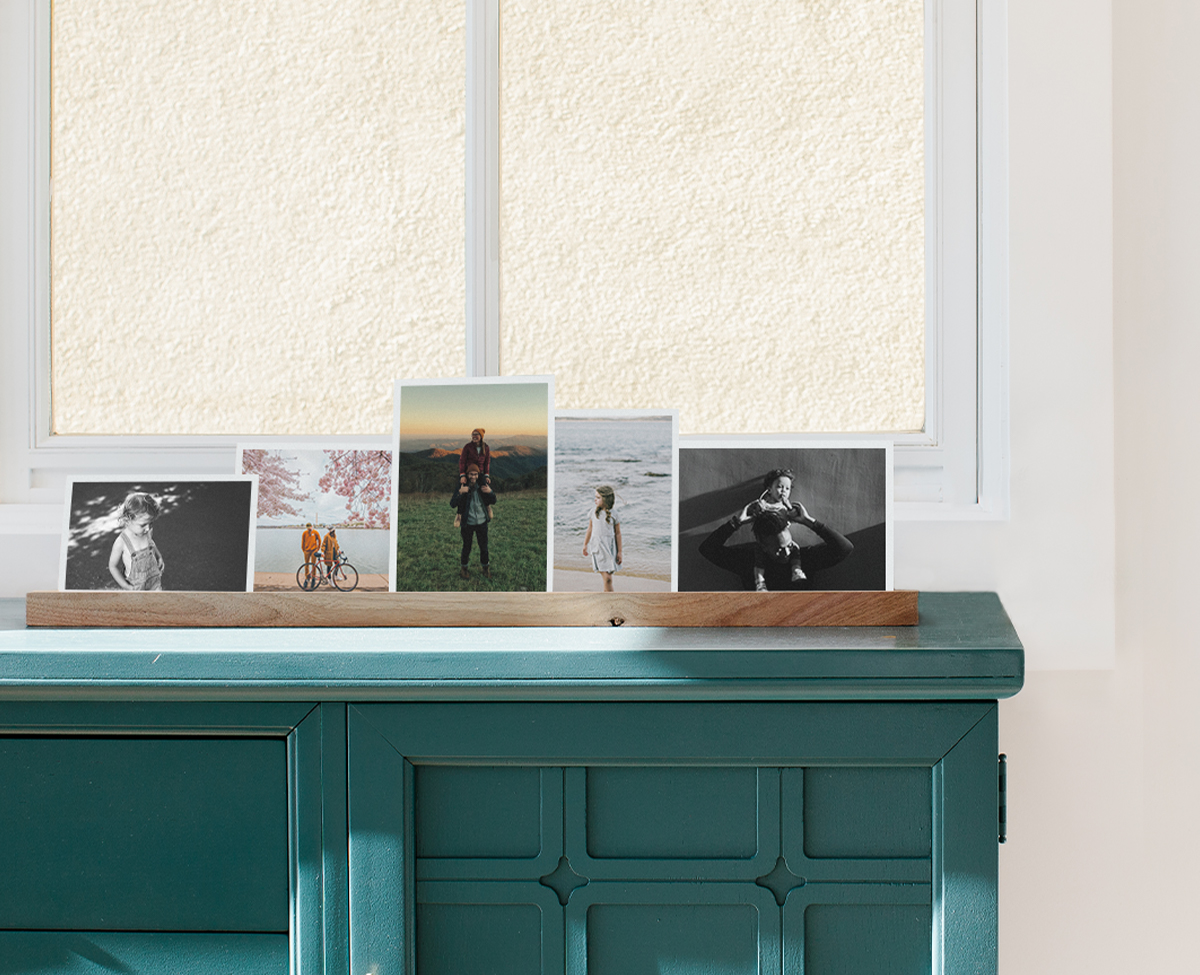 Wooden photo ledge standing on dresser and lined with prints