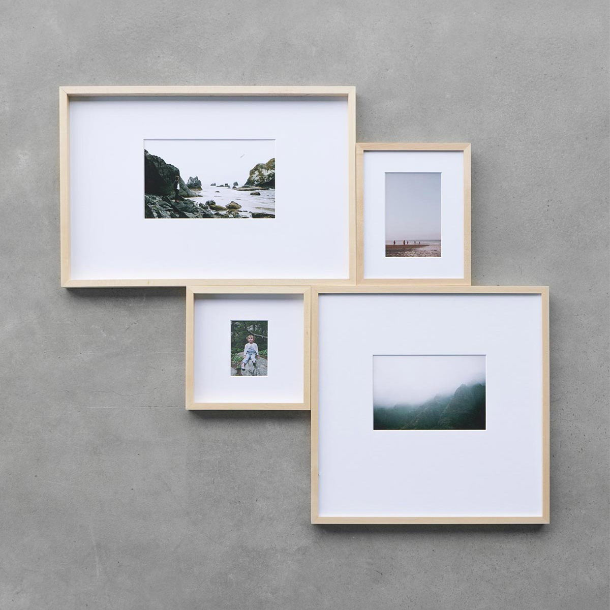 Four small maple frames of different sizes brought together in uniquely shaped gallery wall