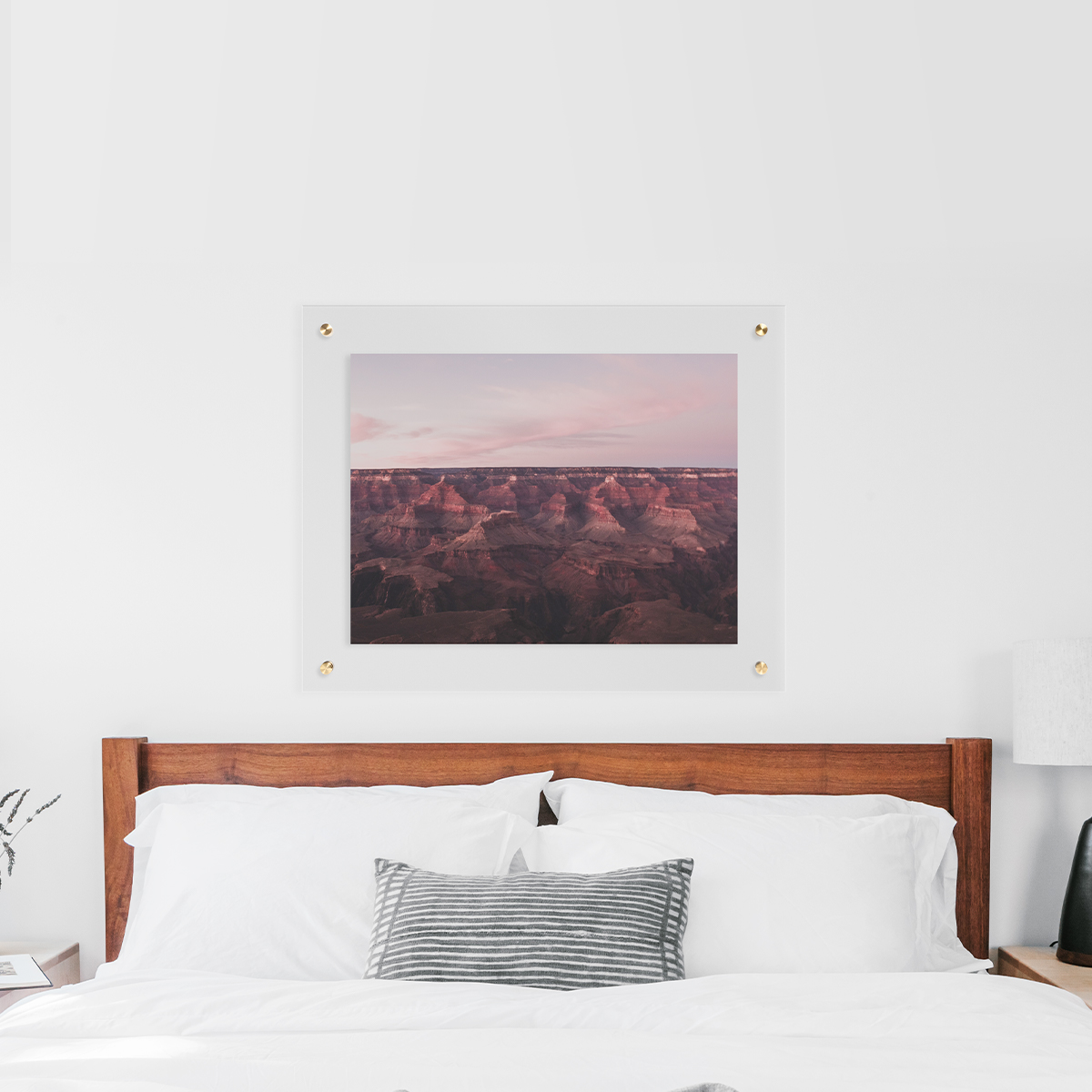Floating frame with desert landscape hanging above bed with white bedspread