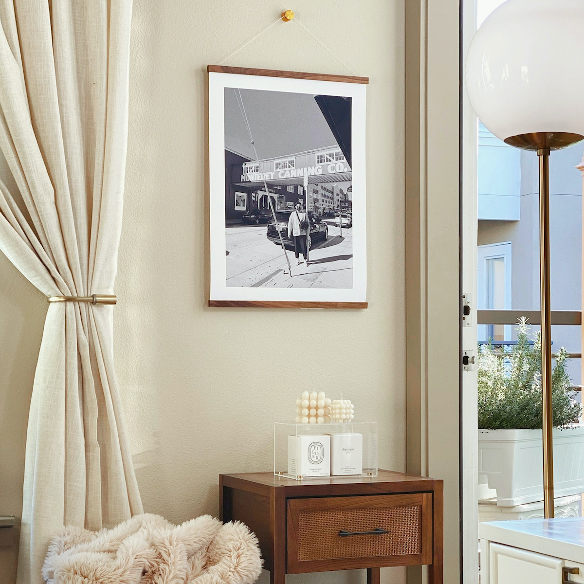 Large Artifact Uprising print featuring photo of man in front of old canning company hanging from print hanger in corner with nightstand