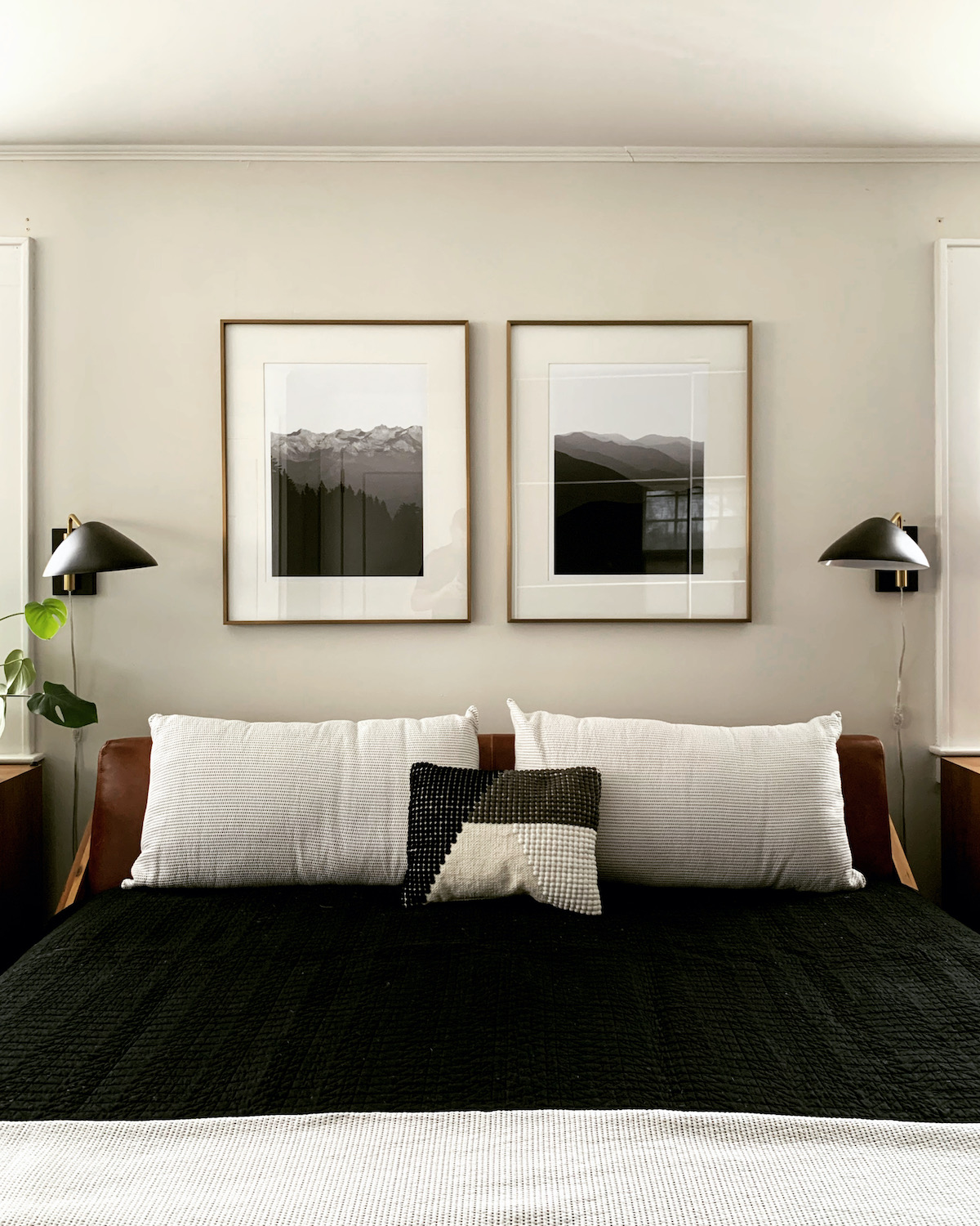 Two framed Artifact Uprising Large Format prints hung above bed featuring black-and-white images of mountainscapes