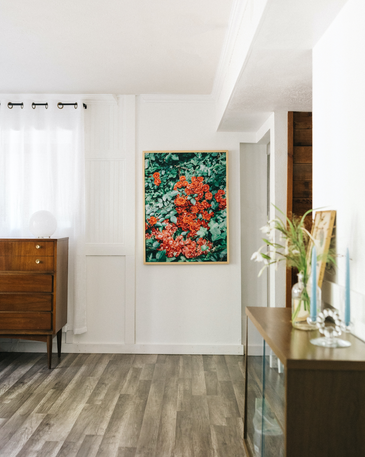 Photo by Kelly Kang of large framed photo featuring red flowers in minimalist roomscape