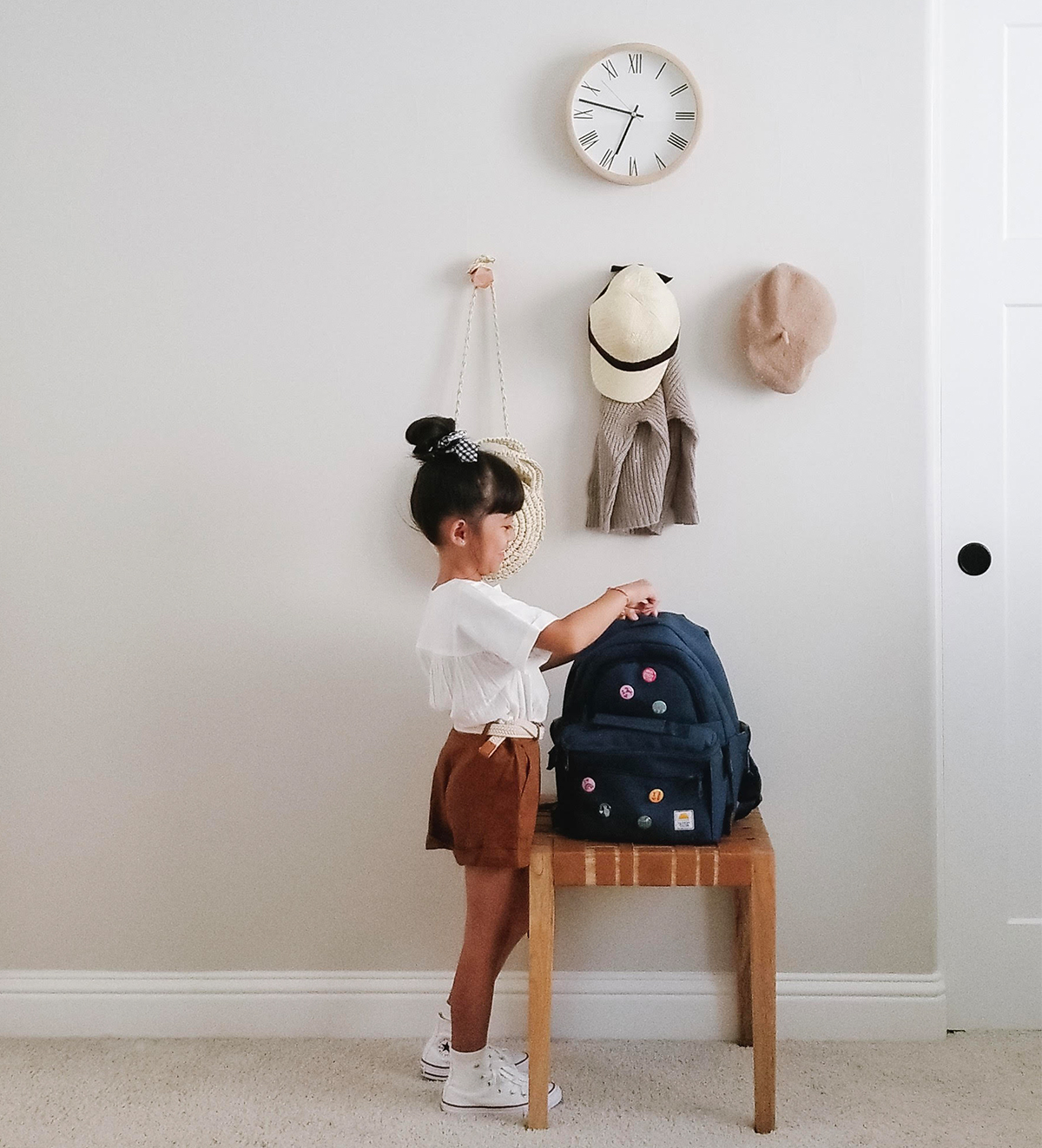 Little girls zipping backpack in front of hats and bags hanging from wall coat hooks