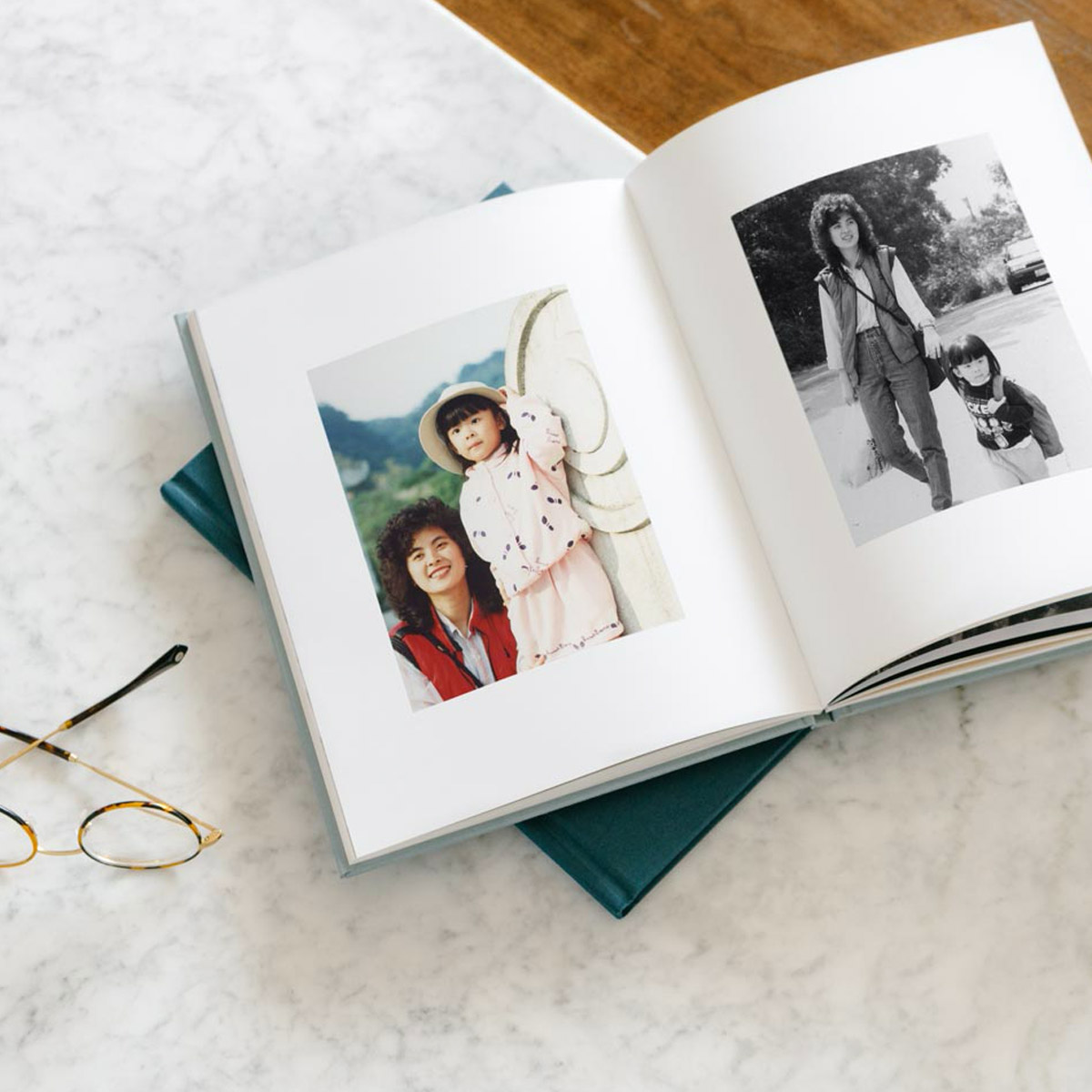 Hardcover photo book opened to photos of mom with daughter