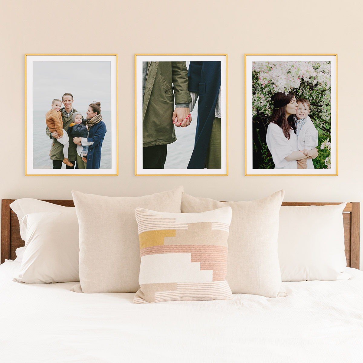 Series of framed family photos above bed