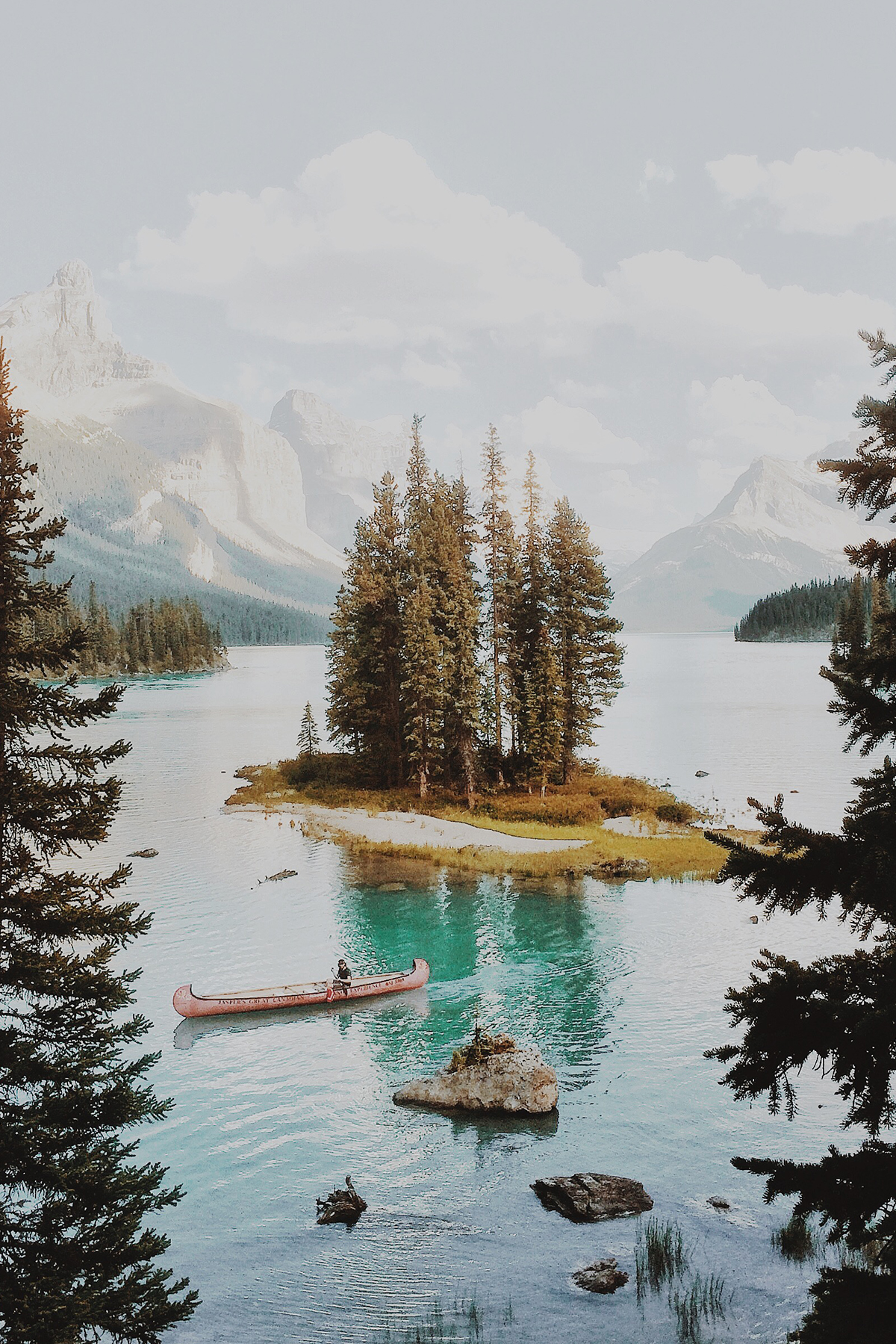 Photo by Alex Strohl of small island in a lake surrounded by mountains
