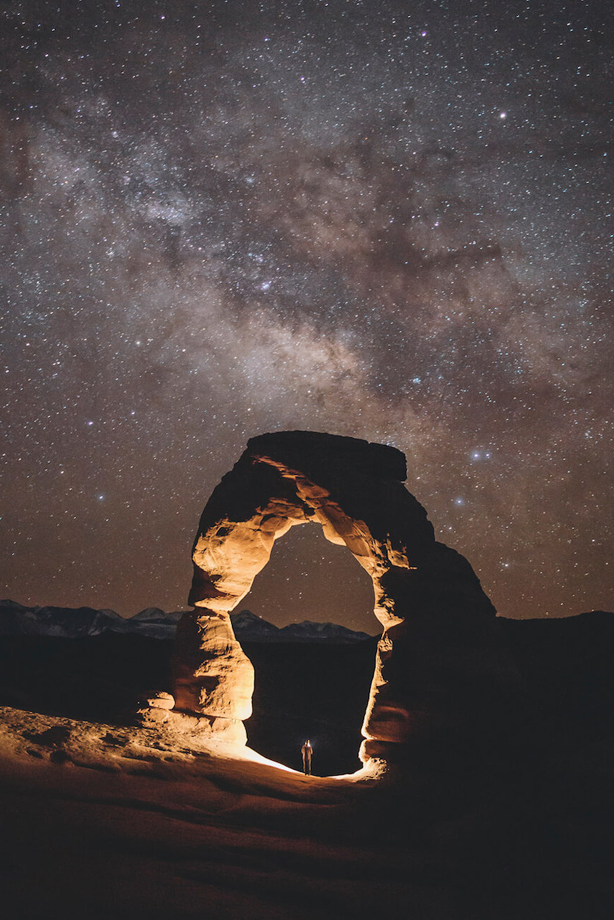 Photo by Garrett King of solitary arch under starry night sky