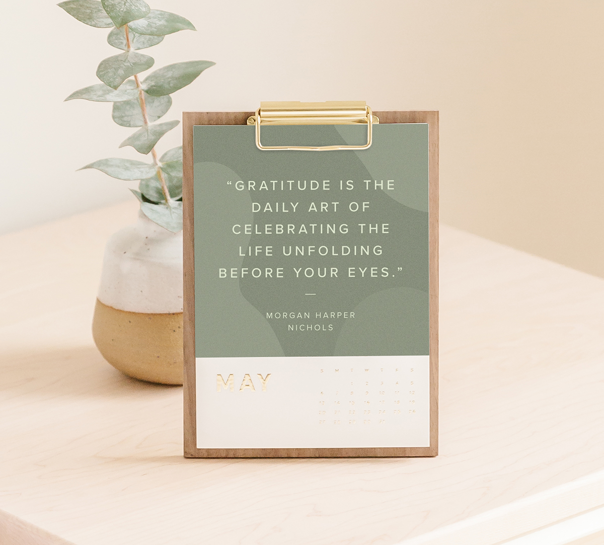 Artifact Uprising Walnut Desktop Calendar with inspiration quote over olive green background for month of May