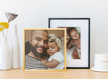 Framed photos of father and daughter on dresser