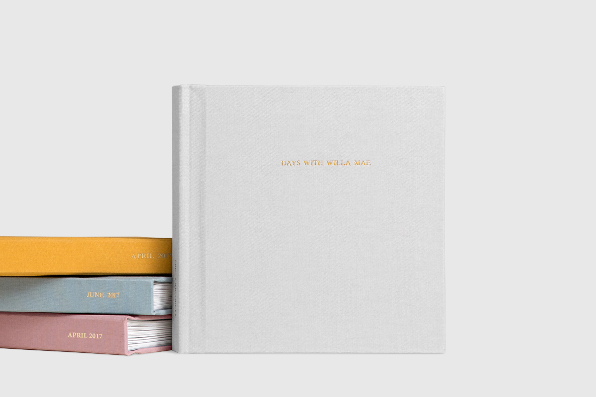 Gray Everyday Photo Book standing next to stack of three different colors