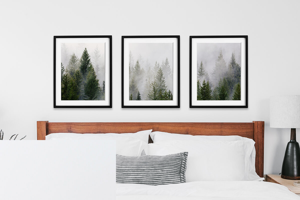 Gallery wall of pine tree forest split into three frames above bed