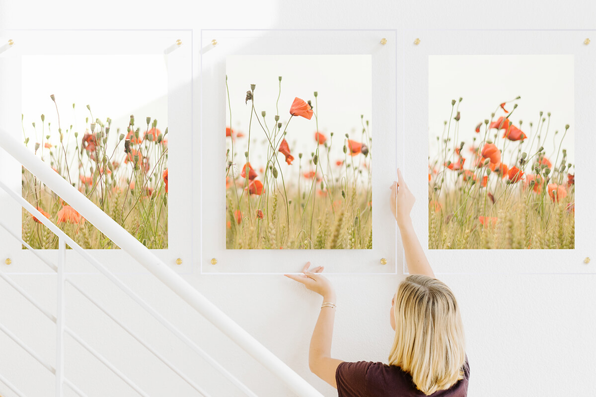 young woman hanging final floating frame in gallery wall of flower field