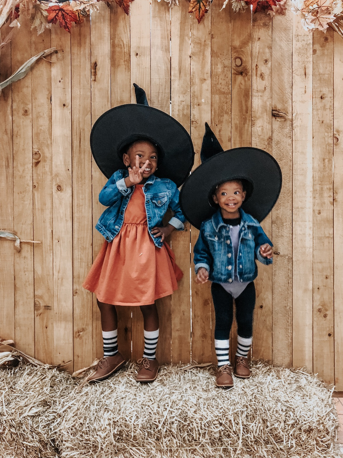 Photo of little girls in Halloween costumes posing for a photo in front of wooden fence