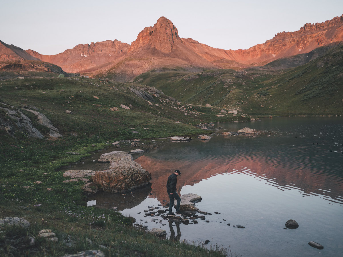 Man at the edge of an alpine lake at golden hour