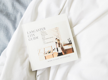 DIY city guide photo album on bed