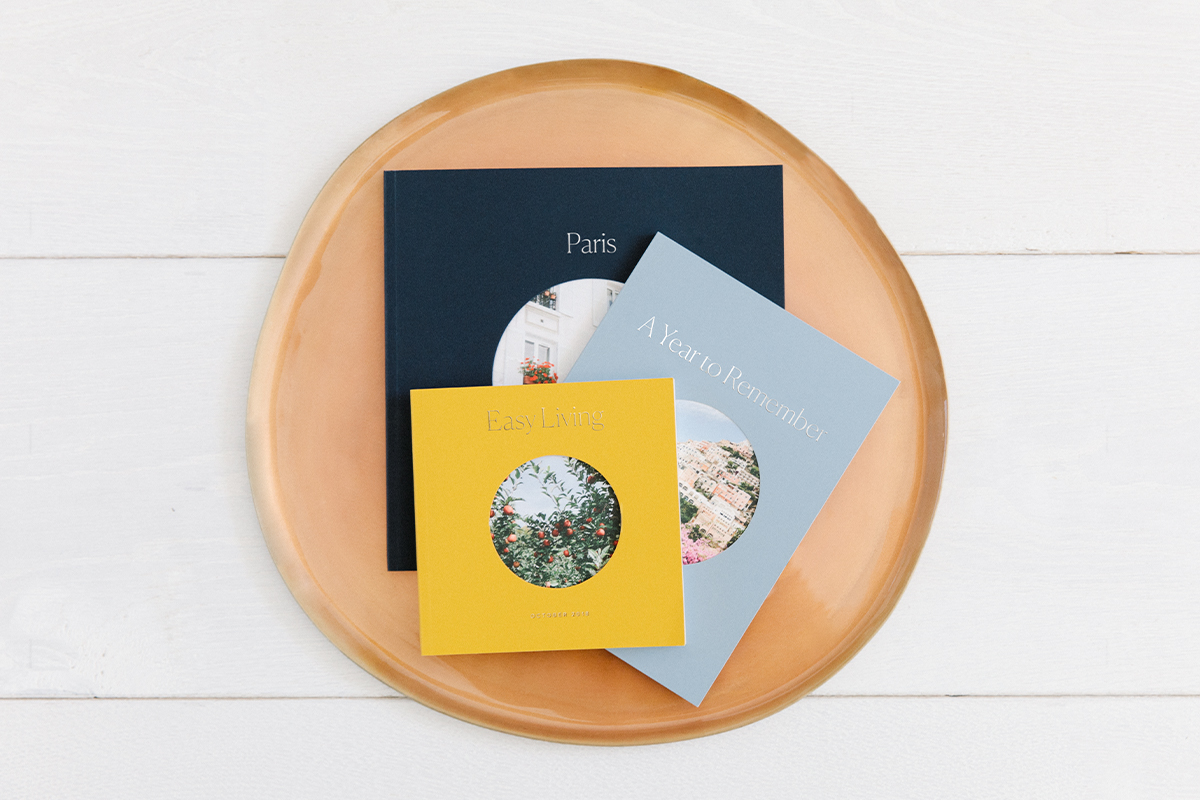 Three photo books arranged in wooden bowl