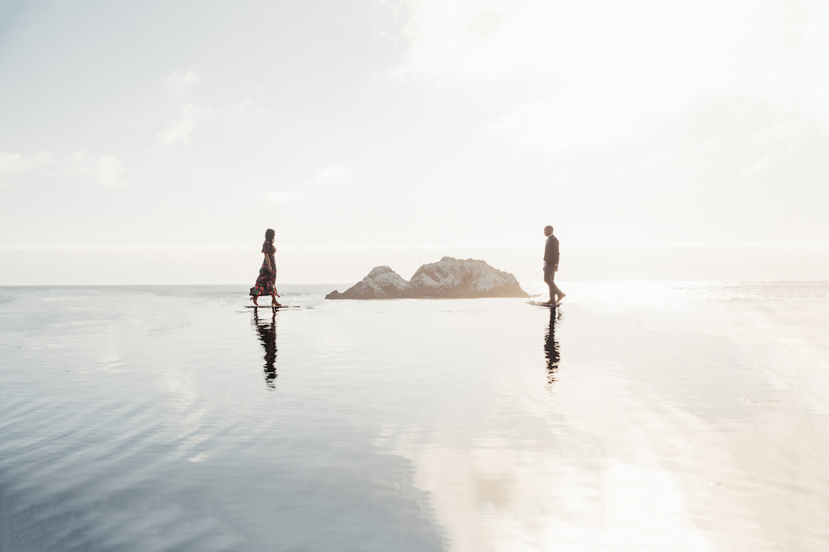 Couple walking toward each other in shallow coastal waters