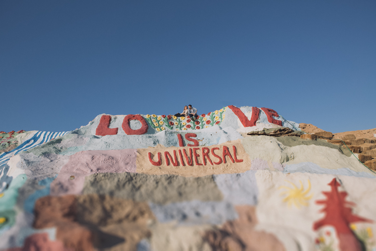 Couple atop hill with graffiti of love is universal