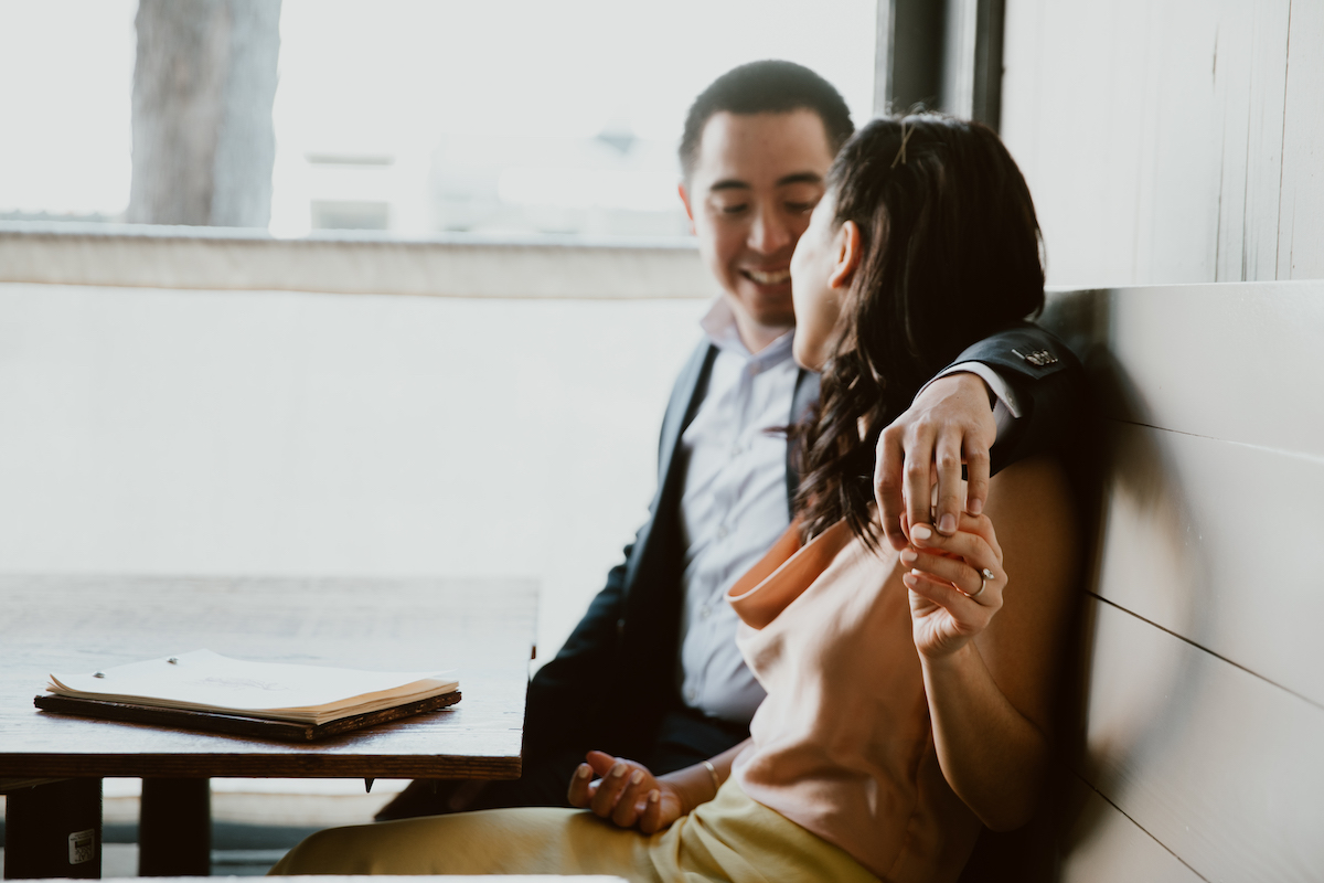 Couple smiling and holding hands in booth seat