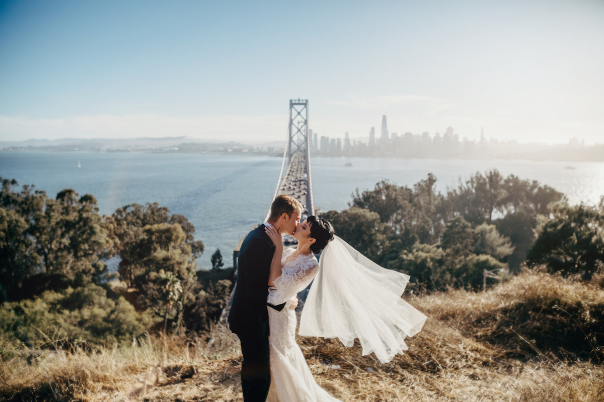 Bride and groom kissing with bridge and city in background