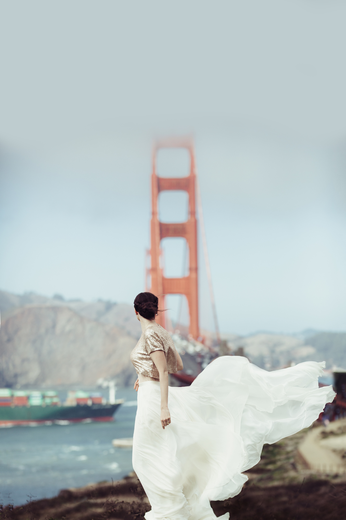 Bride looking away from camera at bridge in the background