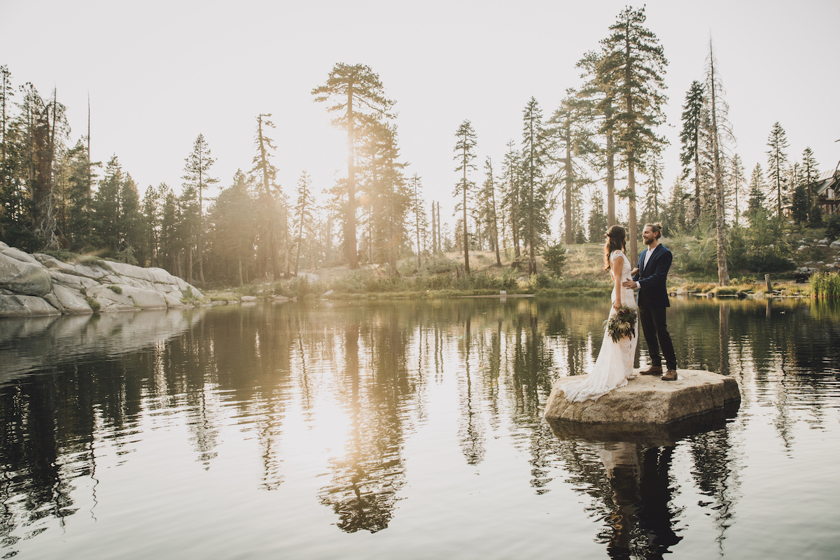Couple standing on small island in pond at golden hour