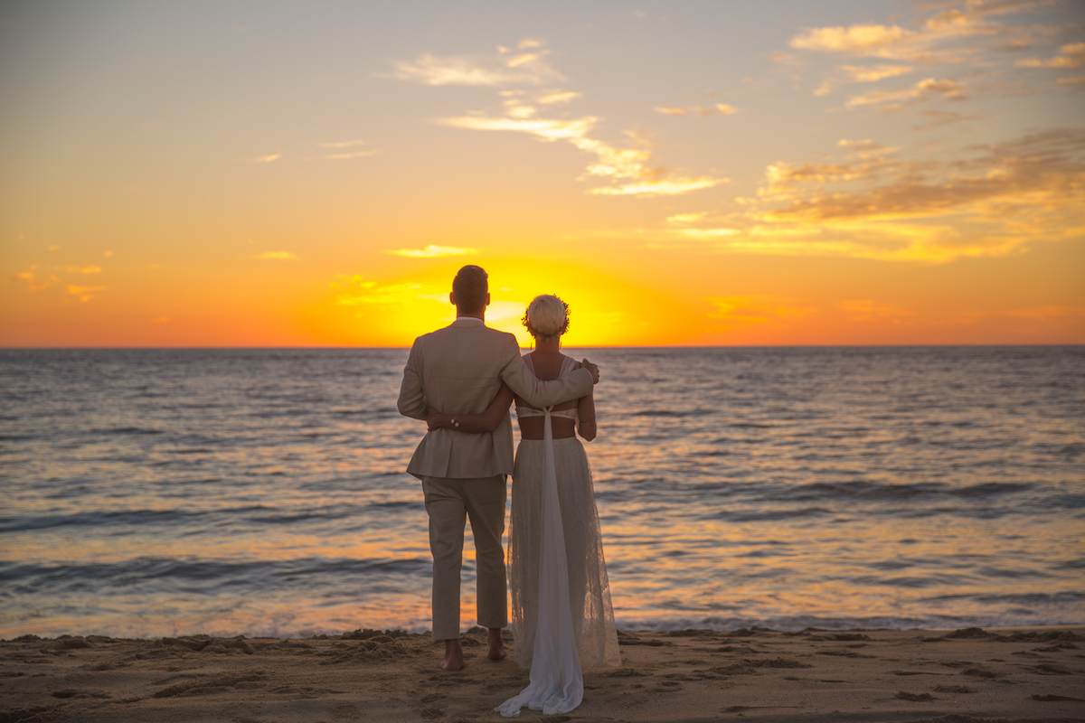 Bride and groom watching the sun set over the ocean