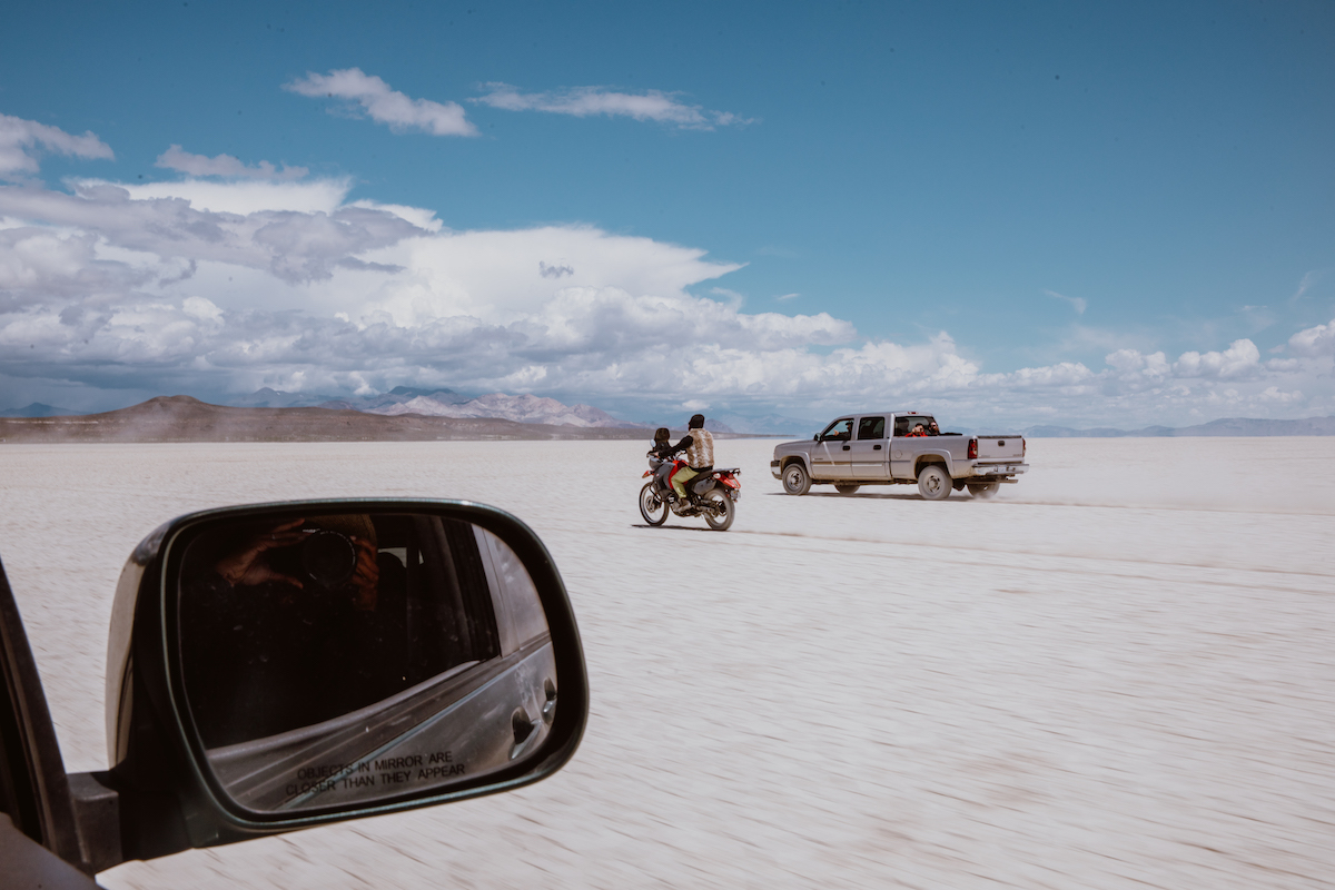 Groom riding motorcycle through the desert