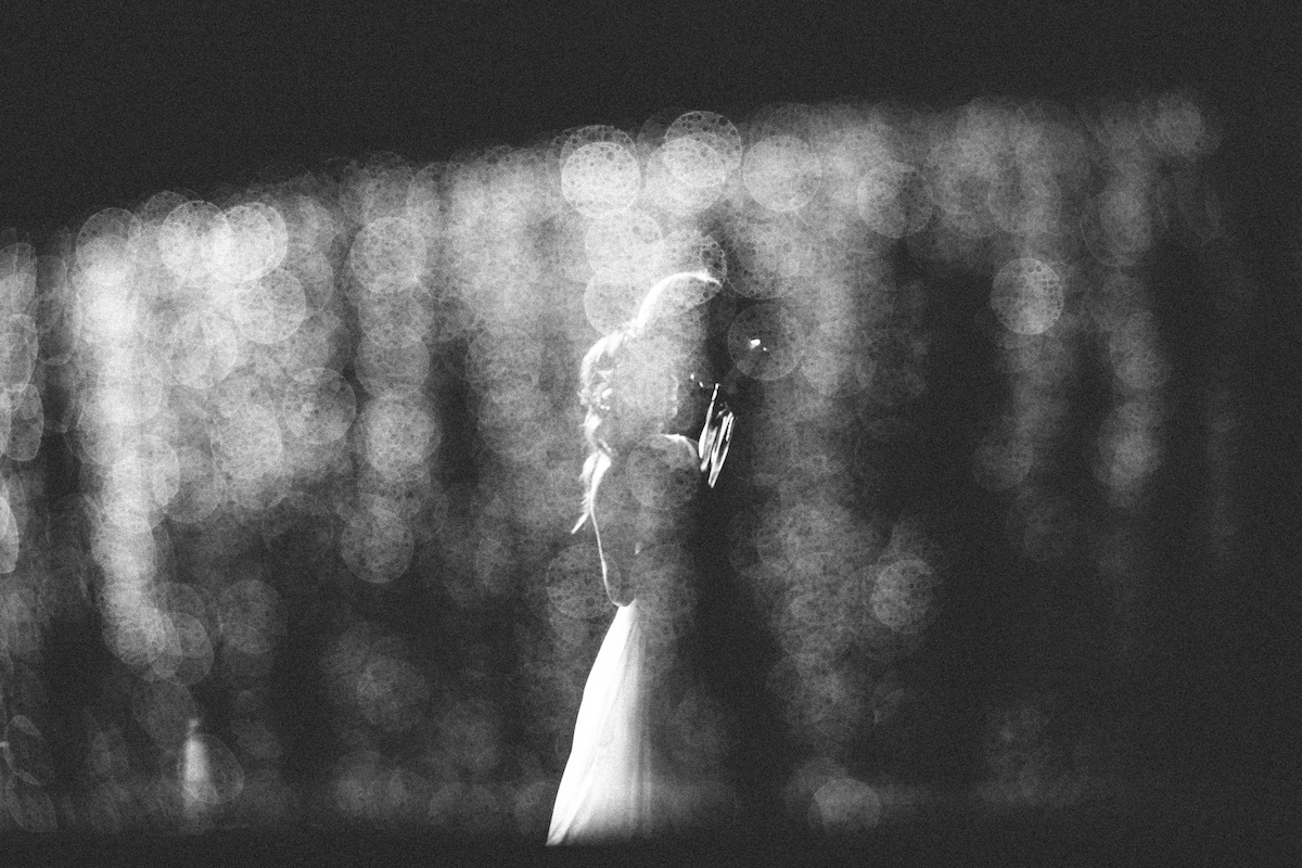 Black and white photo of bride and groom taken through filter