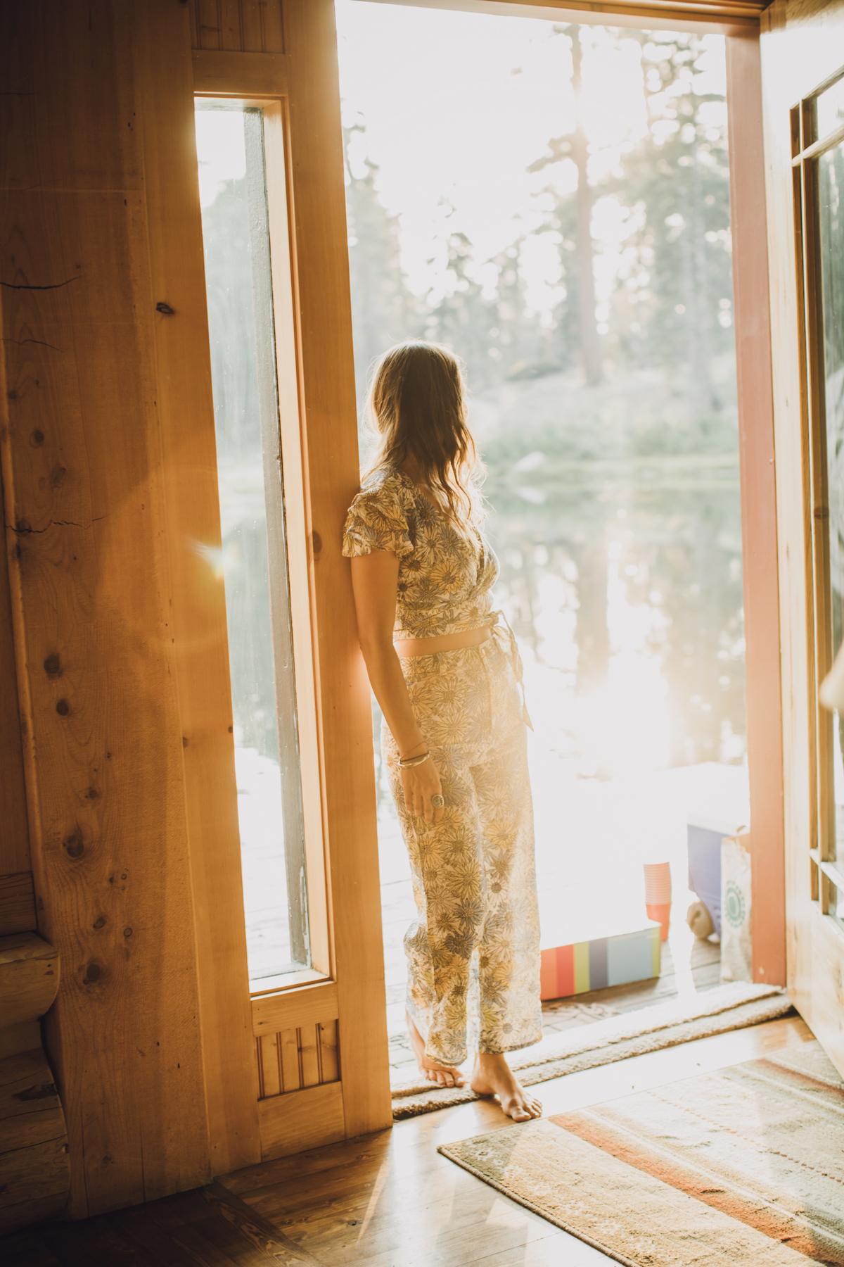 Bride standing in front of doorway flooded with golden light