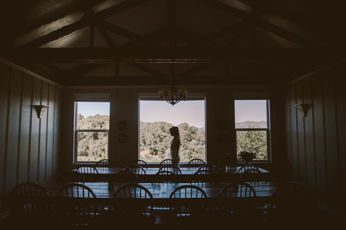 Silhouette of bride standing in front of large windows
