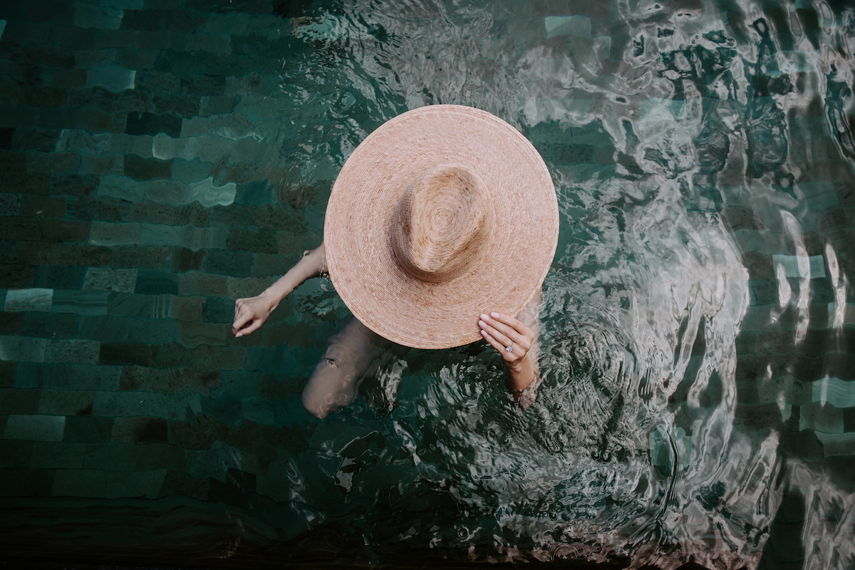 Overhead shot of bride in pool in large sunhat
