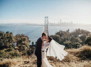 Photo of bride and groom kissing with bridge and city in background