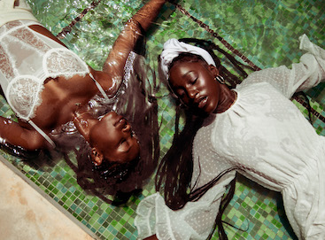 Photo by Andre L. Perry of two Black women laying side by side in water