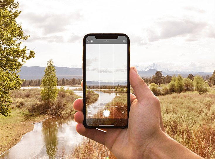 iphone taking photo of scenic wilderness with mountain backdrop