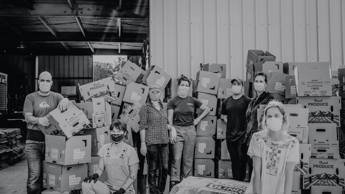 Group photo by Melissa Gayle of CSA workers with masks next to produce boxes