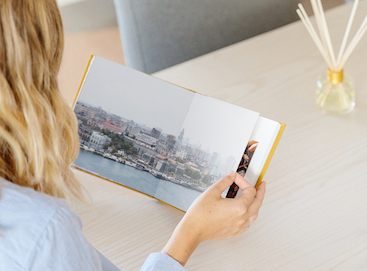 Woman flipping through honeycomb travel album opened to two-page cityscape